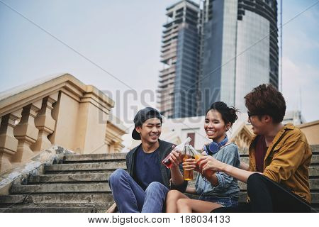 Happy Asian friends sitting on shabby stairs and celebrating their long-awaited gathering with soft drinks, portrait shot