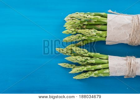 Bunches of green and white asparagus on a blue wooden background