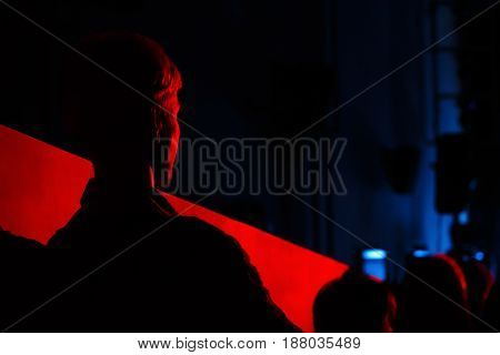 Silhouette spectator is lightened by a blood-red light. Young attractive woman watching thriller or drama movie alone at cinema or theater scared and in shock in dark light.