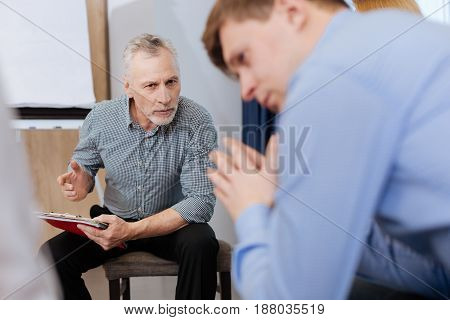 Experienced doctor. Nice bearded senior man sitting on the chair and holding his notes while talking to his patient