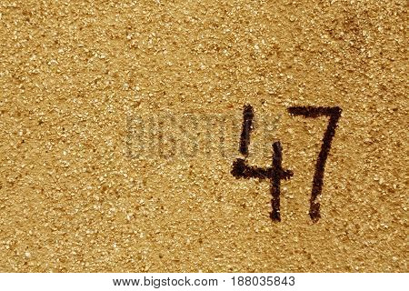 Number Fourty Seven On Orange Plaster Wall.