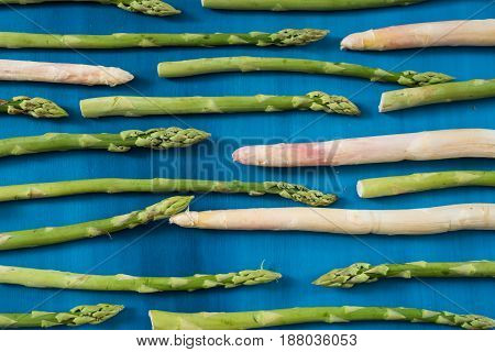 Fresh green asparagus shoots pattern, on a blue wooden background