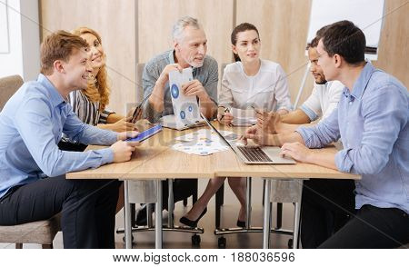 What does it mean. Nice handsome hard working man sitting at the table and pointing at the diagram while working with his colleagues