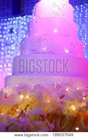 Multi tiered wedding cake decorated with flowers Wedding party evening