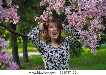 Emotional woman in the garden among the lilacs. People