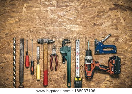 A set of hand tools in a row for working on wood, on the panel of OSB. With free space for text. Top view. Background.