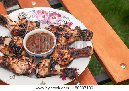 Fried chicken thighs with sauce lie on a wooden table