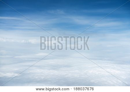White clouds and blue sky view from airplane window. Beautiful cloudscape from sky aerial view. Beauty of nature view from above the sky and clouds.