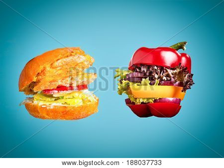 Healthy sandwich with fresh pepper, onion, salad lettuce and unhealthy harmful hamburger. Concept of diet.