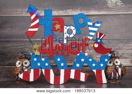 A Happy Fourth of July sign with two owl figurines for the holiday