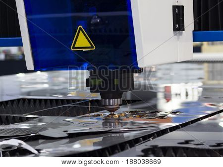 Technology High precision manufacturing concept.CNC Industrial laser cutting steel metal with bright sparks/ Intermarch 2017 Industrial Machinery Exhibition at Bitech Thailand - May 2017