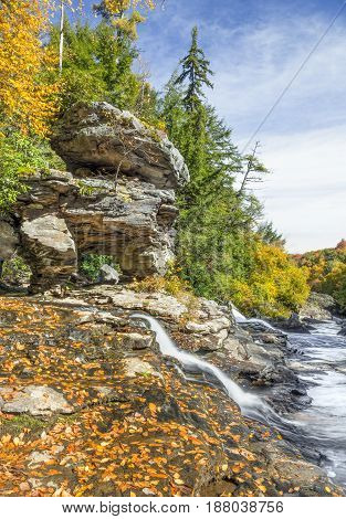 Muddy Creek splashes past interesting rock formations and autumn leaves as it joins the Youghiogheny River in Swallow Falls State Park Maryland.