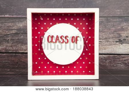 A class of sign against a wood background