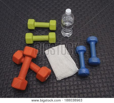 Colorful Hand Weights Towel And Water On Workout Mat