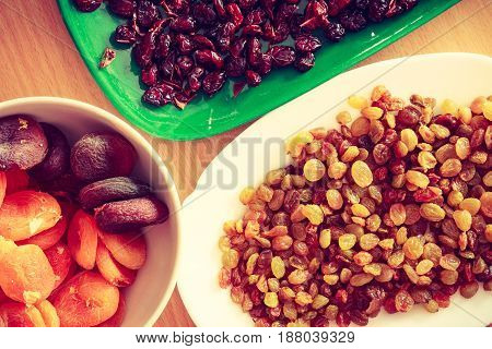 Delicacies dry fruits cake additives concept. Plates with dried cranberries apricots and raisins.