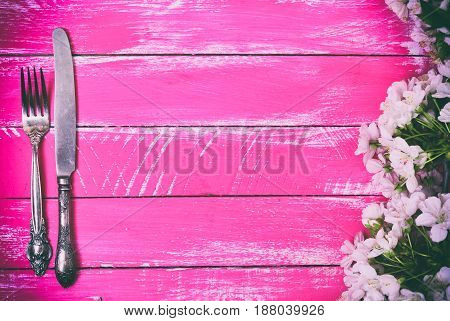 Iron fork and knife on a pink wooden background empty space in the middle