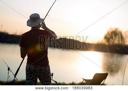 Young man fishing at pond and enjoying hobby activities