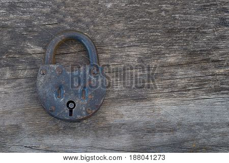 Grungy and rusted steel metal lock on a old wooden table background. Left position.