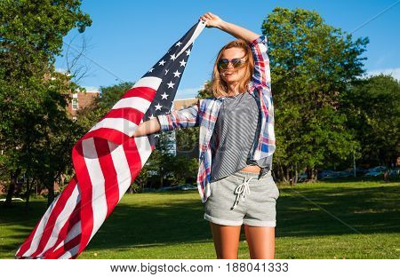 Young happy patriot girl holding United States flag
