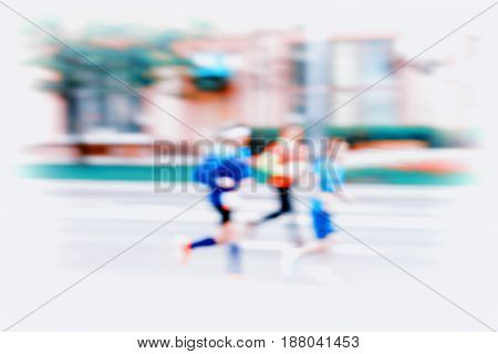 Group of three young runners in moving, blur effect, unrecognizable faces. City marathon on road. Sport, fitness and healthy lifestyle concept. For modern backdrop, wallpaper or banner design, place for your text