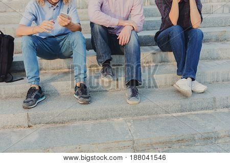 Group of people with gadgets outdoor, copy space. Company of three unrecognizable friends have rest on stairs in street. Modern technologies and communication problem concept