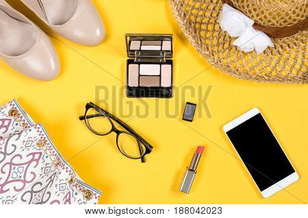 Arrangement of essential woman summer accessories on bright yellow background, top view