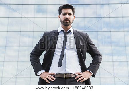 Arabic serious businessman or worker in black suit with tie and shirt with beard standing in front of an office building on green grass in summer day.