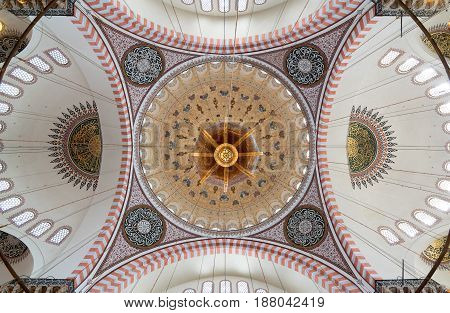 Istanbul, Turkey - April 19, 2017: Decorated ceiling of Suleymaniye Mosque showing intersection of four domes with the main big dome Istanbul Turkey