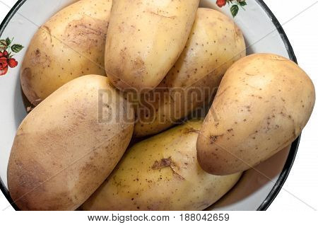 Some raw uncleaned potatoes lie in an iron bowl