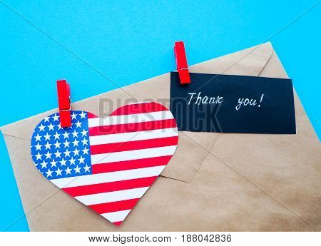 envelope USA flag hanging on colorful pegs clothespin on a line against blue background. United States of America Thank you