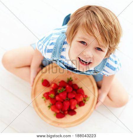 Happy Kid With A Tray Of Tasty Ripe Strawberries