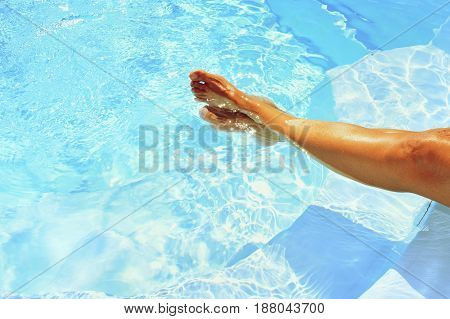 Legs in the pool with clean water in hot sunny day. Summer background for traveling and vacation. Holiday idyllic.