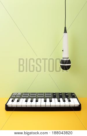 Musical instrument - MIDI keyboard and vokal microphone for a karaoke hangs down on top on a flavovirent background.