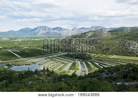 A photo of landscapes in Croatia. Beautiful farmer's fields and water canals. Summer nature in the Mediterranean. Road trip to Dubrovnik.