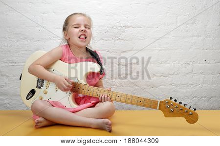 Young girl rock guitarist executes solo on an electric guitar.