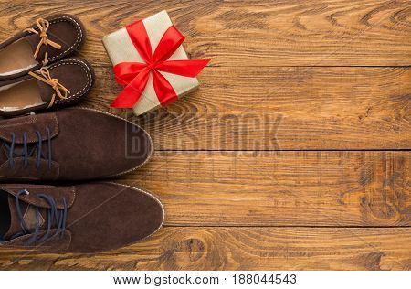 Happy Fathers Day card background on rustic wood with male and child shoes, copy space