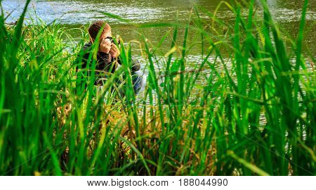 The photographer the young guy sits on the bank of the river it is visible behind a high green grass it photographes the nature