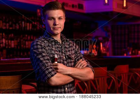 The man smoke an electronic cigarette at the vape shop. Vape bar. The guy is looking at the camera