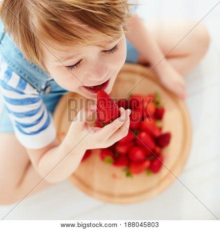 Cute Happy Kid Eating Tasty Ripe Strawberries