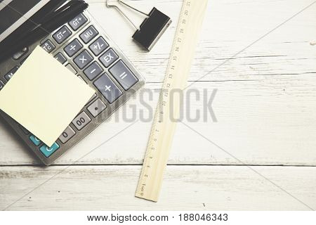 sticky paper on calculator on wooden table