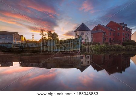 The old cargo ship in the river channel Exe. Near the apartment houses. Colorful sunset. Exeter. Devon. England