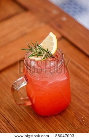 Strawberry soda drinks in tropical tree show wooden table and plate in nice atmosphere.