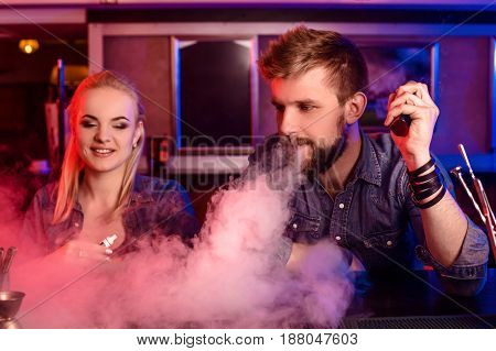 A man and woman smoking electronic cigarette in a vape bar. Vape shop