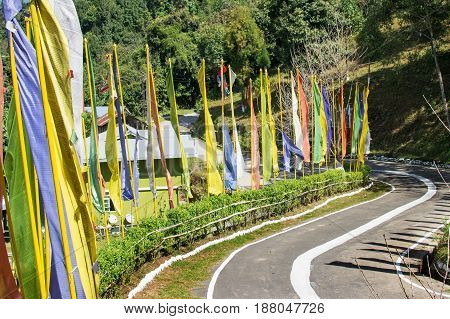 Beautiful way to Ralong Monastery at Ralong colourful Buddist prayer religious flags waving on the side of road . Ralong is full of scenic natural vista in background in Sikkim India.