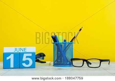 June 15th. Day 15 of month, calendar on yellow background with office suplies. Summer time at work. Global Wind Day. Tax DAY.