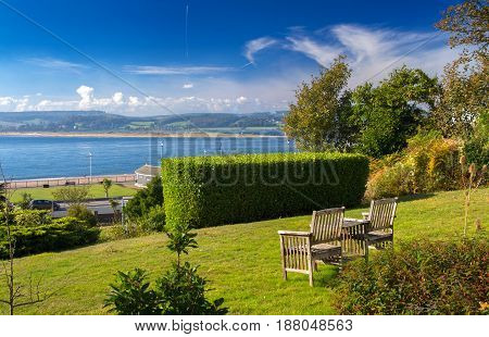 Bench or chairs with a table on the lawn with a magnificent view of the fusion of the Exe River with the English Channel (La Manche). City of Exmouth. Devon. UK