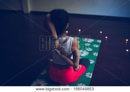 yoga instructor sits in asana on green Mat