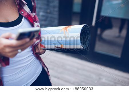 girl holding a blue yoga Mat in hand