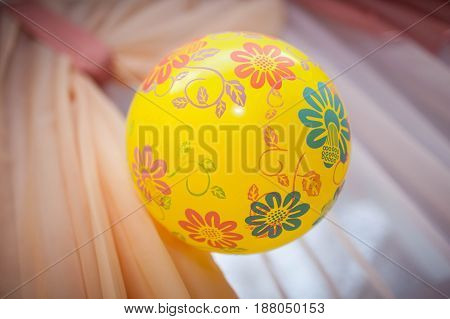 yellow ball with patterns weighs on top