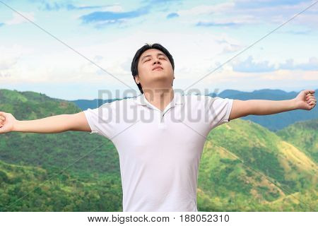 Asian man is taking deep breath in the nature environment